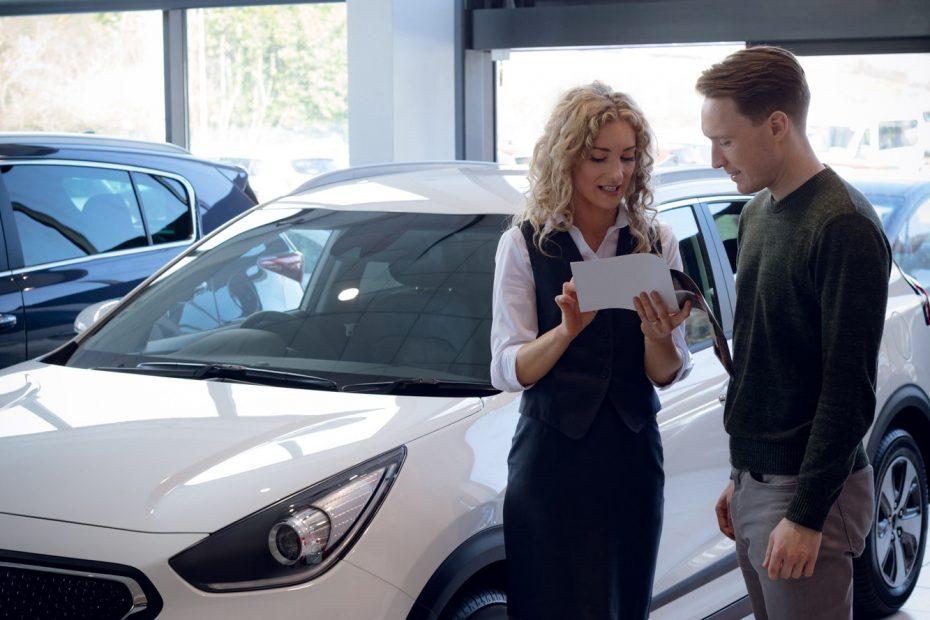 Confident saleswoman showing brochure to customer in car showroom