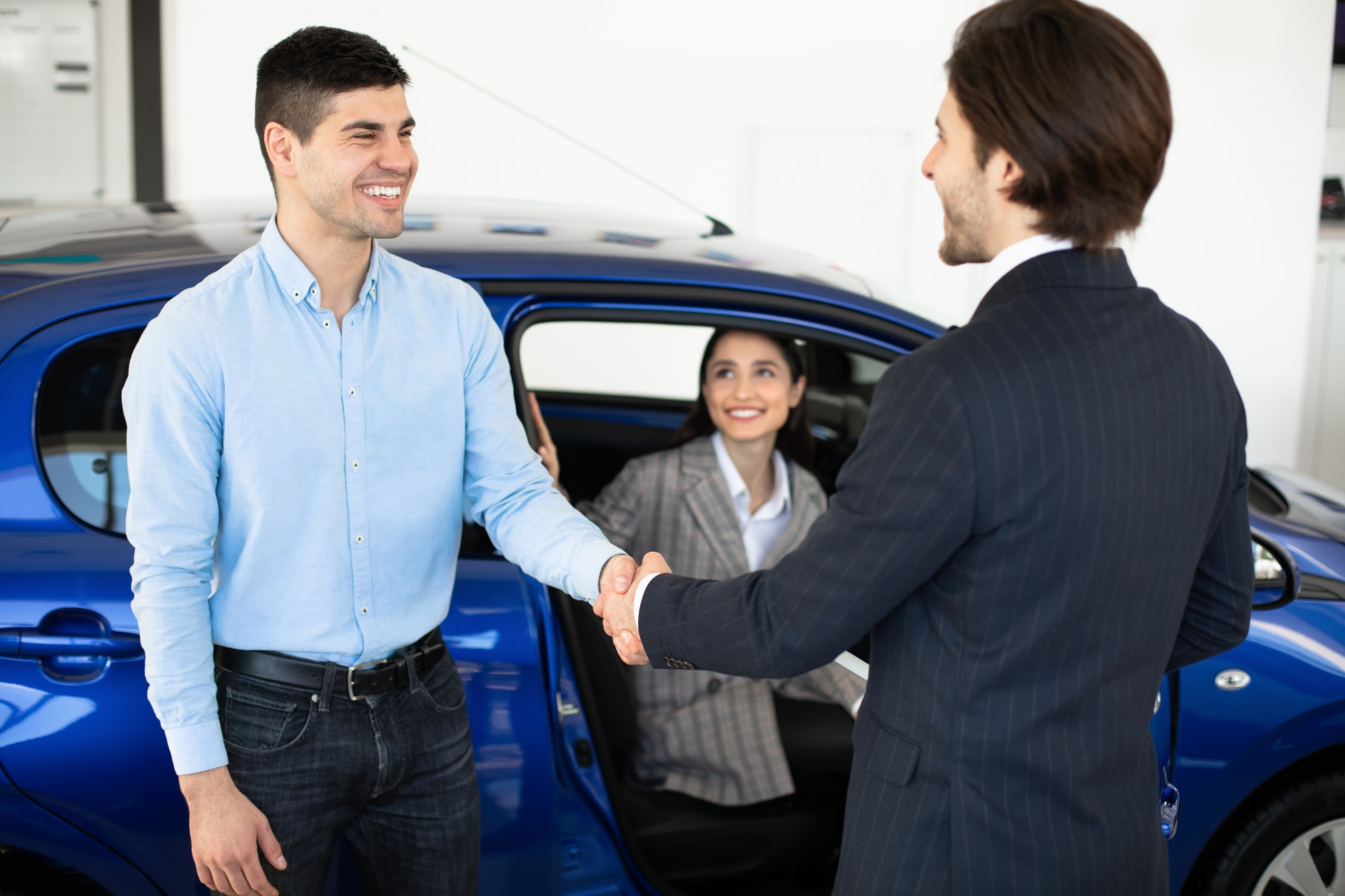 Man Shaking Hands With Car Sales Manager In Dealership Store