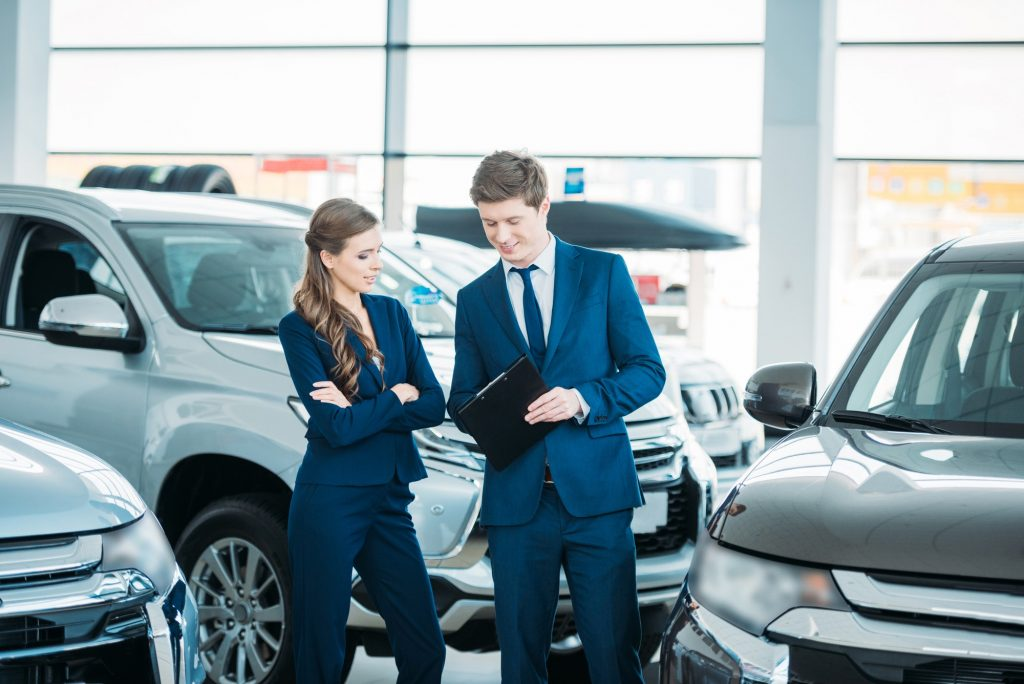 Sales managers of a car showroom standing and looking at clipboard